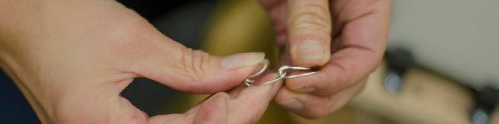 Hands making jewelry