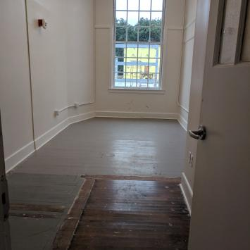 Photo of artist studio with large window, white walls and wooden floor