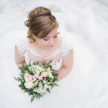White woman in white wedding dress with flowers