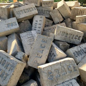 Pile of adobe bricks with words imprinted in them