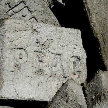 Adobe brick with the word PEACE pressed into it