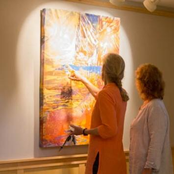 Two women looking at a painting